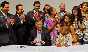 National Jewish Health President and CEO Michael Salem, MD, several students from the Kunsberg School and others share a laugh after the governor signed a law establishing a tax credit for contributions to Kunsberg and other hospital-based schools.