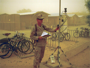 Iraq veteran Dr. Richard Meehan testing air quality in a dust storm in the Middle East.