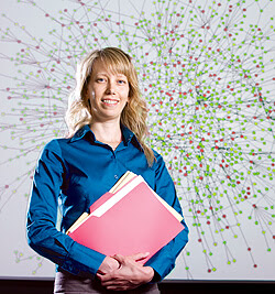 Sonia Leach, PhD, director of bioinformatics, stands in front of a graph that highlights important biological relationships discovered with the help of a new supercomputer at National Jewish Health.