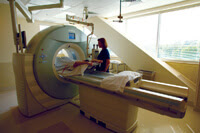 Woman conducting a CT scan on a patient