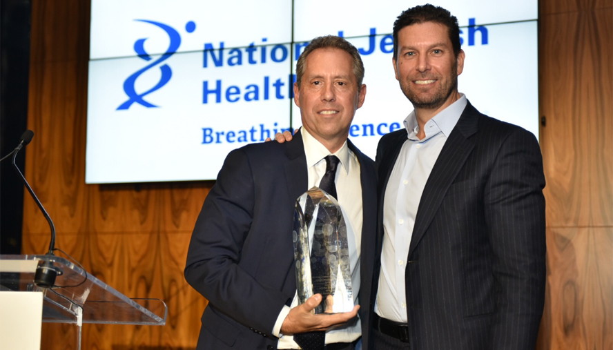 Jonathon K. Yormak of East End Capital presents David A. Falk of Newmark Knight Frank with the National Jewish Health Irving Borenstein Memorial Award. Yormak received the same award in 2016.